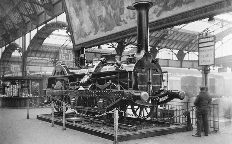 La locomotive Crampton n°80 lors de son exposition en gare de l'Est à Paris entre 1931 et 1946, carte postale, photo : Paul Gollemant, Collection Cité du Train